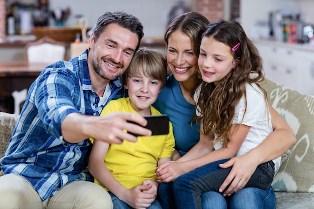 Glückliche familie, die ein selfie am handy nimmt
