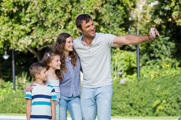 Glückliche familie, die ein selfie auf handy nimmt