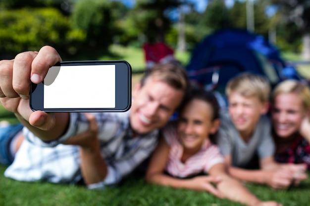 Glückliche familie, die ein selfie im park nimmt