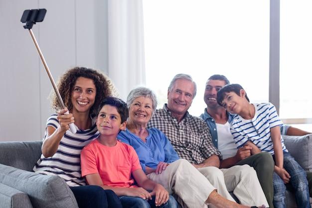 Glückliche familie, die ein selfie im wohnzimmer nimmt