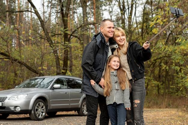 Glückliche familie, die ein selfie in der natur nimmt