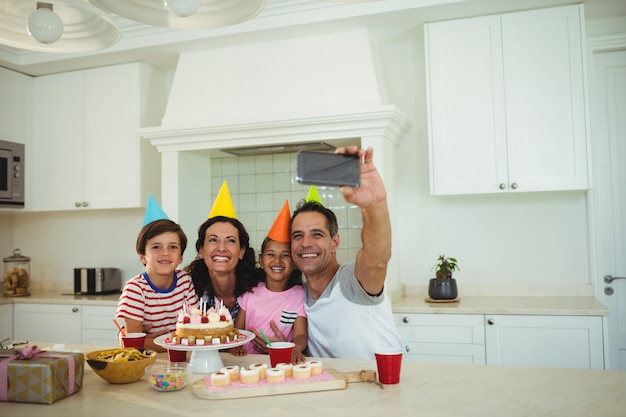 Glückliche familie, die ein selfie nimmt, während sie einen geburtstag feiert