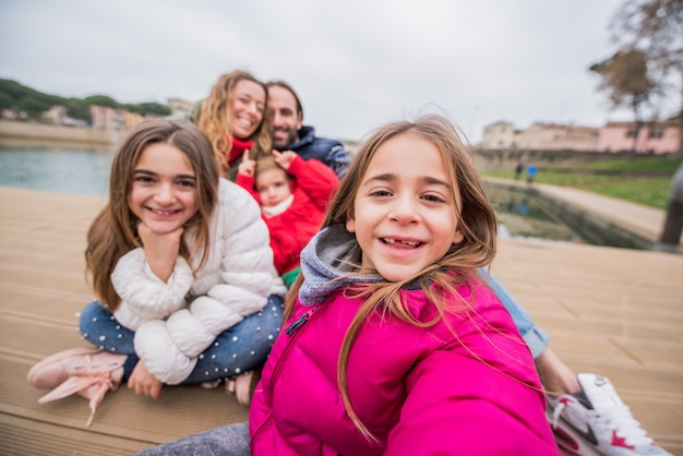 Glückliche familie, die ein selfie zusammen im freien nimmt
