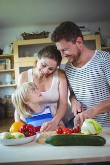 Glückliche familie, die einander beim zubereiten des salats in der küche betrachten