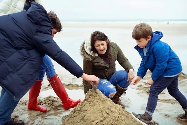 Glückliche familie, die eine sandburg baut