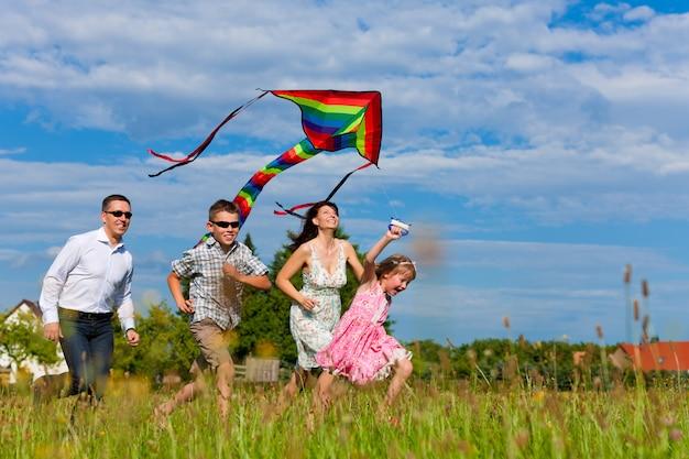 Glückliche familie, die einen drachen auf den gebieten fliegt
