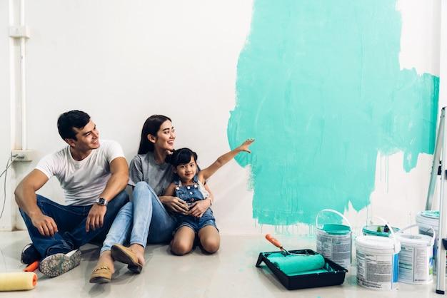 Glückliche familie, die einen farbroller benutzt und wände in ihrem neuen zuhause malt