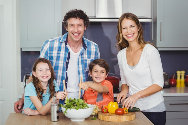 Glückliche familie, die einen gemüsesalat zubereitet