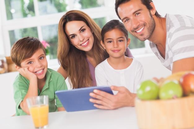 Glückliche familie, die einen tabletten-pc verwendet