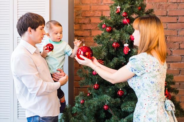 Glückliche familie, die einen weihnachtsbaum mit kugeln im wohnzimmer schmückt.