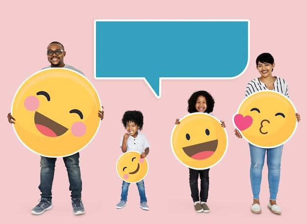 Glückliche familie, die emoji-ikonen hält