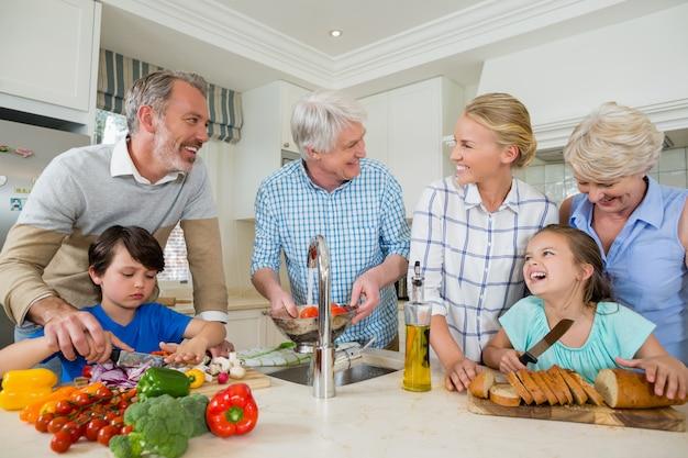 Glückliche familie, die essen in der küche zubereitet