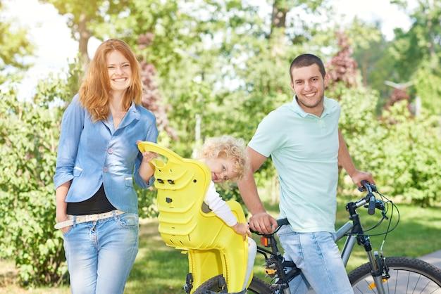 Glückliche familie, die fahrrad im park fährt