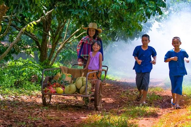 Glückliche familie, die frische organische früchte auf einem bauernhof auswählt.