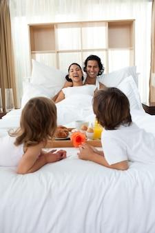 Glückliche familie, die frühstückt, liegend auf dem bett