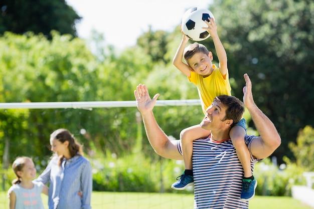 Glückliche familie, die fußball im park spielt