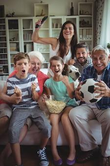 Glückliche familie, die fußballspiel im fernsehen im wohnzimmer sieht