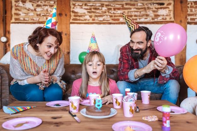 Glückliche familie, die geburtstag des kleinen mädchens feiert