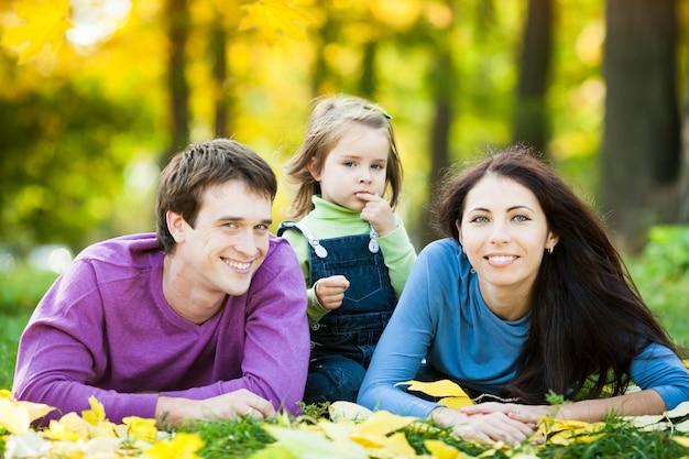 Glückliche familie, die gegen unscharfen blätterhintergrund im herbstpark liegt?
