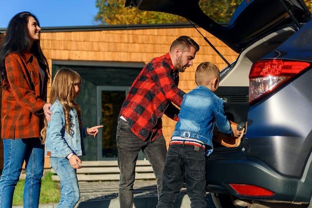 Glückliche familie, die gepäck in den kofferraum eines autos packt, bevor sie in ein neues zuhause zieht oder in den urlaub fährt