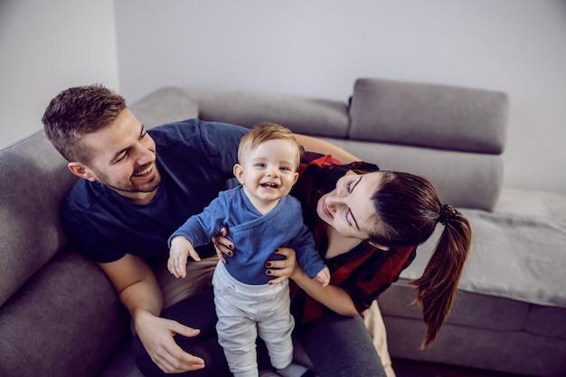 Glückliche familie, die gute zeit zusammen verbringt. mama und papa spielen mit ihrem einzigen geliebten sohn.