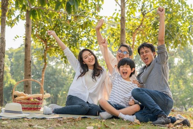 Glückliche familie, die hände erhebt und zusammen lächelt, während sie im park picknicken