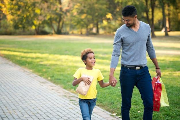 Glückliche familie, die hände hält und zusammen im park geht