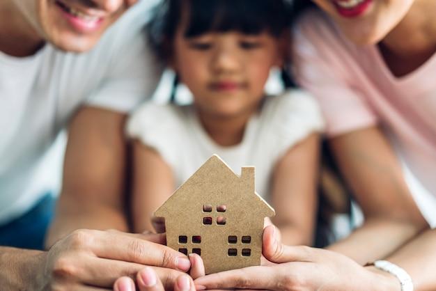 Glückliche familie, die haus in den händen hält immobilienkonzept