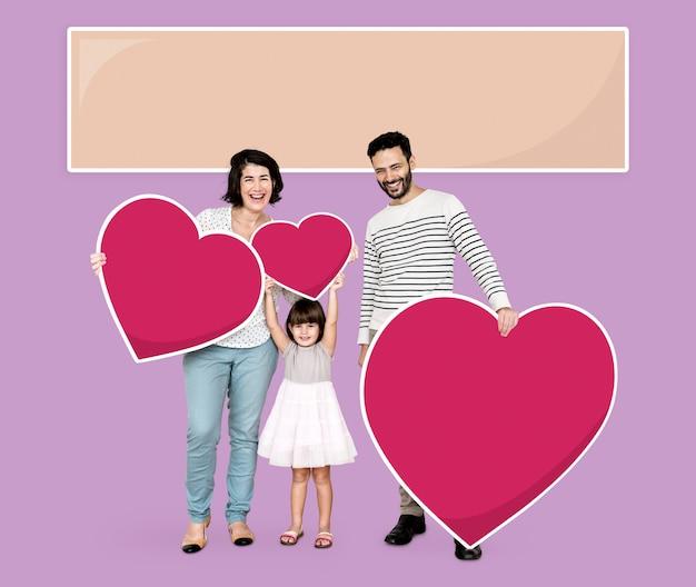 Glückliche familie, die herzikonen hält
