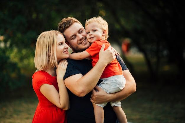 Glückliche familie, die ihr kind umarmt