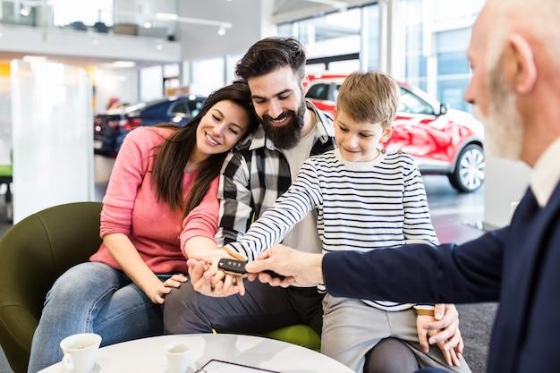 Glückliche familie, die im autohaus ein neues auto kauft.