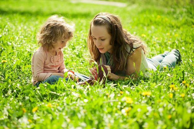 Glückliche familie, die im frühlingspark auf grünem frass spielt