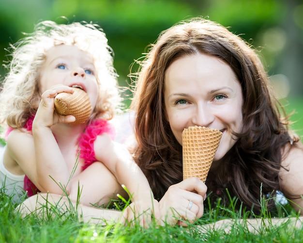 Glückliche familie, die im frühlingspark gegen unscharfen grünen hintergrund eis im freien isst