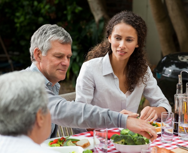 Glückliche familie, die im garten isst
