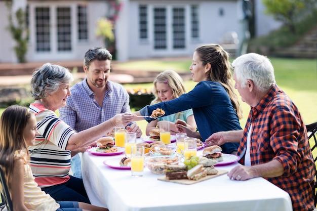 Glückliche familie, die im garten zu mittag isst