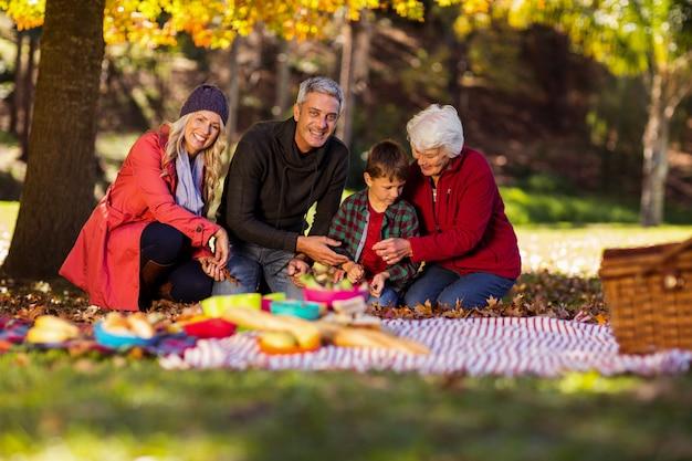 Glückliche familie, die im herbst im park sitzt