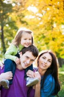 Glückliche familie, die im herbstpark huckepack spielt