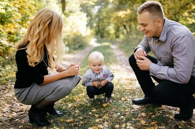 Glückliche familie, die im herbstpark spielt und lacht