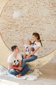 Glückliche familie, die im minimalistic studioraum mit backsteinmauer auf hintergrund spielt