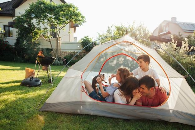 Glückliche familie, die im nockenzelt am park genießt