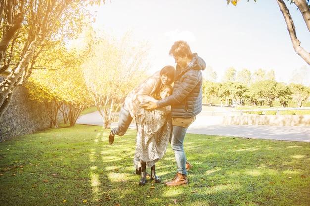 Glückliche familie, die im park am sonnigen tag spielt