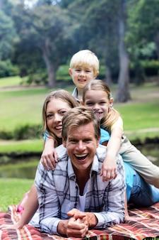 Glückliche familie, die im park liegt