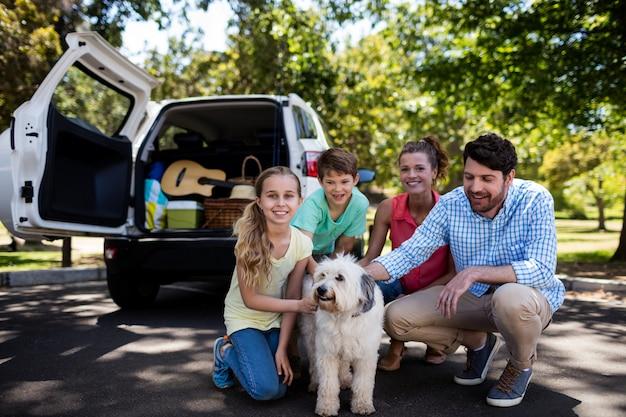 Glückliche familie, die im park mit ihrem hund sitzt