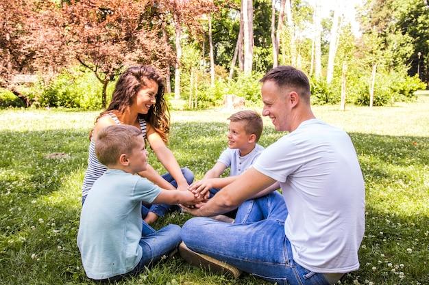 Glückliche familie, die im park sitzt