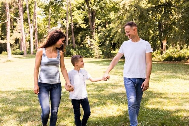 Glückliche familie, die im park spazierengeht