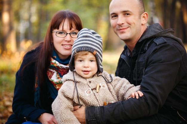 Glückliche familie, die im park stillsteht