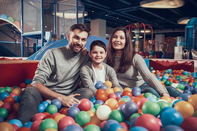 Glückliche familie, die im pool mit bällen sitzt