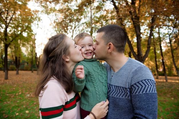 Glückliche familie, die im schönen herbstpark stillsteht