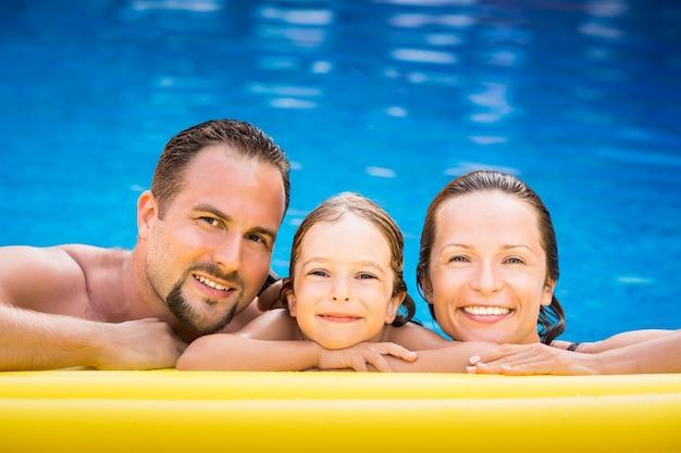 Glückliche familie, die im schwimmbad spielt