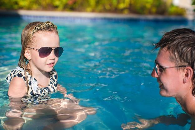 Glückliche familie, die im swimmingpool sich entspannt